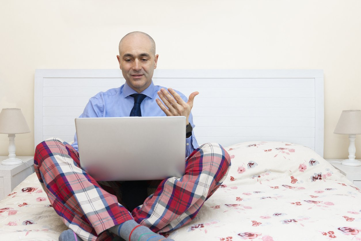 an working with a laptop in a bed wearing a shirt and tie and pajama pants