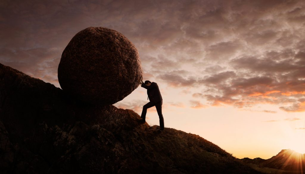 Man rolling boulder up a hill with much effort